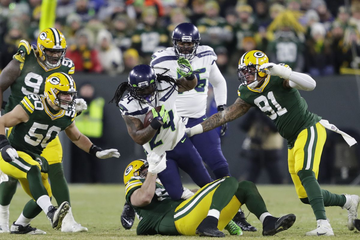 Seattle Seahawks running back Marshawn Lynch is tackled by Green Bay Packers defensive end Dean Lowry in a NFC Divisional Round playoff football game at Lambeau Field.