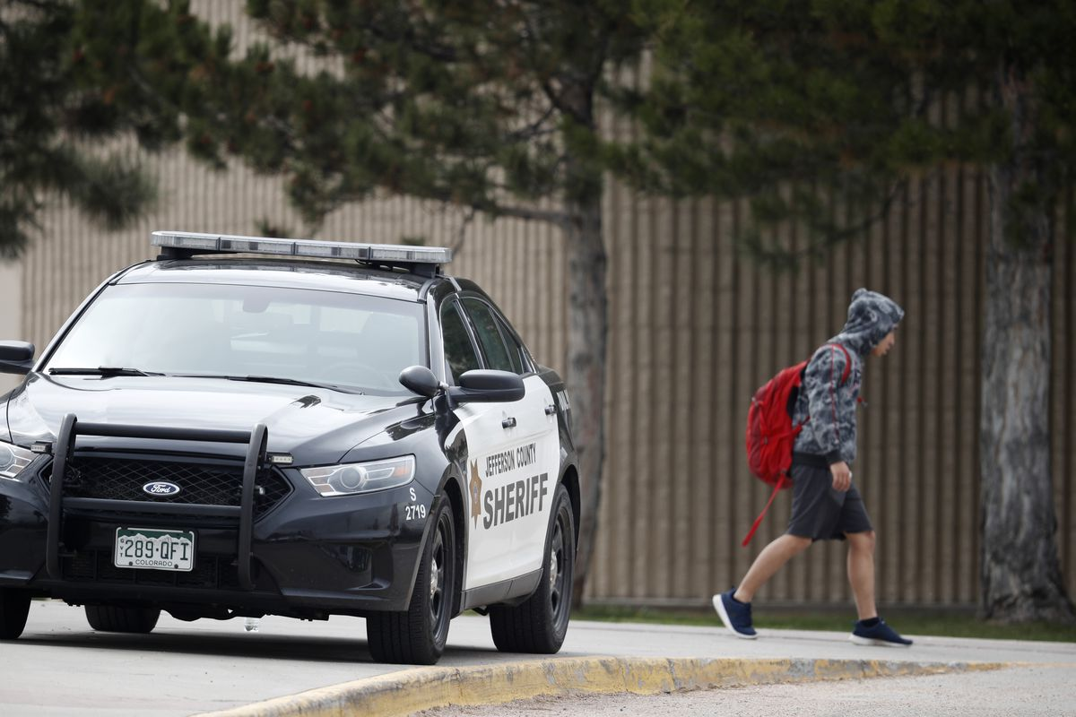 A student leaves Columbine High School late Tuesday, April 16, 2019, in Littleton, Colorado. Following a lockdown at Columbine High School and other Denver area schools, authorities say they are looking for a woman suspected of making threats.
