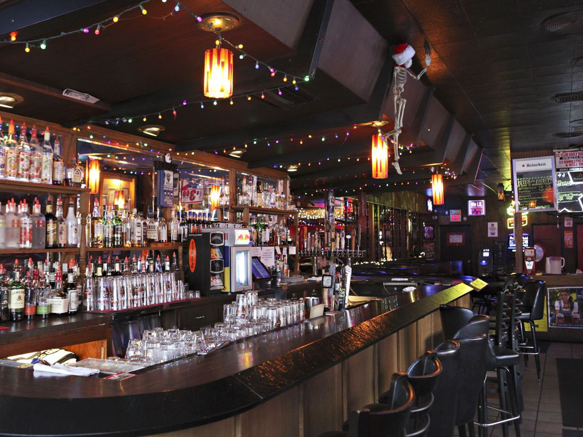 A dark bar that's positively crowded with bottles of booze