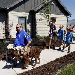 Purple Heart veteran U.S. Army Sgt. 1st Class Travis Vendela, left, and his family head into their new home in Huntsville, Weber County, on Friday, July 3, 2020.