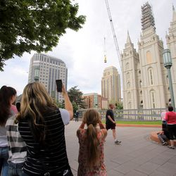 Onlookers gather to watch as the Angel Moroni statue is lowered to the ground by workers from Jacobsen Construction as they remove it from the Salt Lake Temple of The Church of Jesus Christ of Latter-day Saints in Salt Lake City on Monday, May 18, 2020.The temple is currently undergoing renovation.