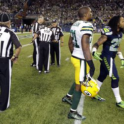 Officials discuss the final play of the game as Green Bay Packers' Charles Woodson, second from right, and Seattle Seahawks' Earl Thomas, right, leave the field in the second half of an NFL football game, Monday, Sept. 24, 2012, in Seattle. The final play was ruled a Seattle touchdown as the Seahawks defeated the Packers 14-12.
