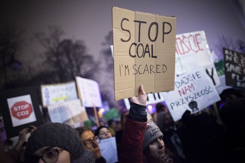 """A protester holds a sign saying, """"Stop coal, I'm scared."""""""