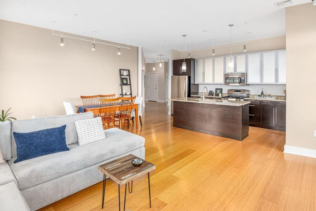 An open kitchen-dining room-living room area with a kitchen island and then there's furniture.