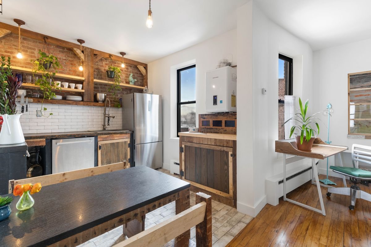 An eat-in kitchen with exposed brick, a wooden table, and several planters.