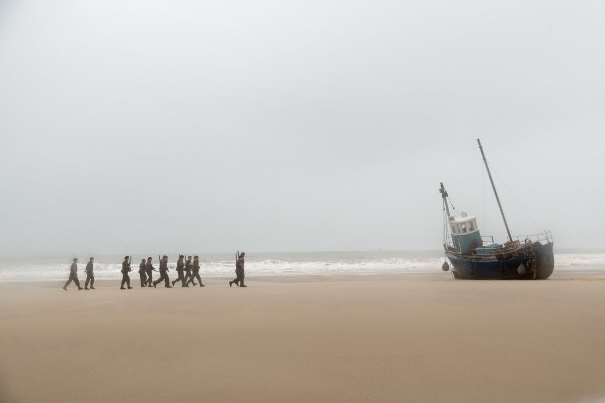 A group of soldiers, led by Alex (Harry Styles), heads for a beached boat in Dunkirk.