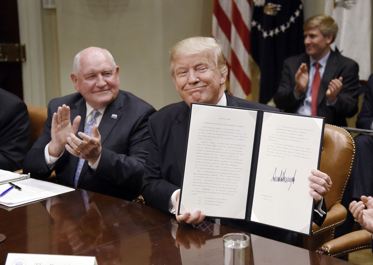 WASHINGTON, D.C. - APRIL 25: (AFP-OUT) US President Donald Trump signs the Executive Order Promoting Agriculture and Rural Prosperity in America as Agriculture Secretary Sonny Perdue looks on during a roundtable with farmers in the Roosevelt Room of the W