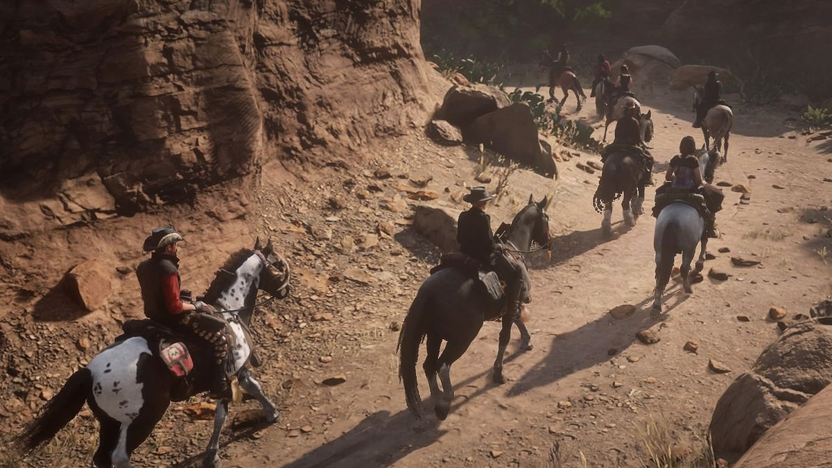 A group of riders and horses in a canon from the Red Dead Redemption 2 video game