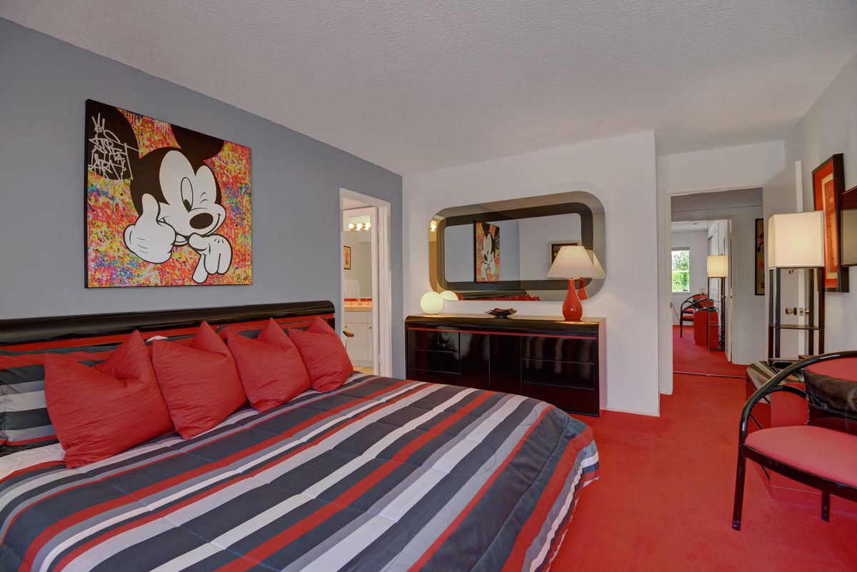 A striped red, white, and blue bed sits on red carpet with a Mickey Mouse poster above the bed.