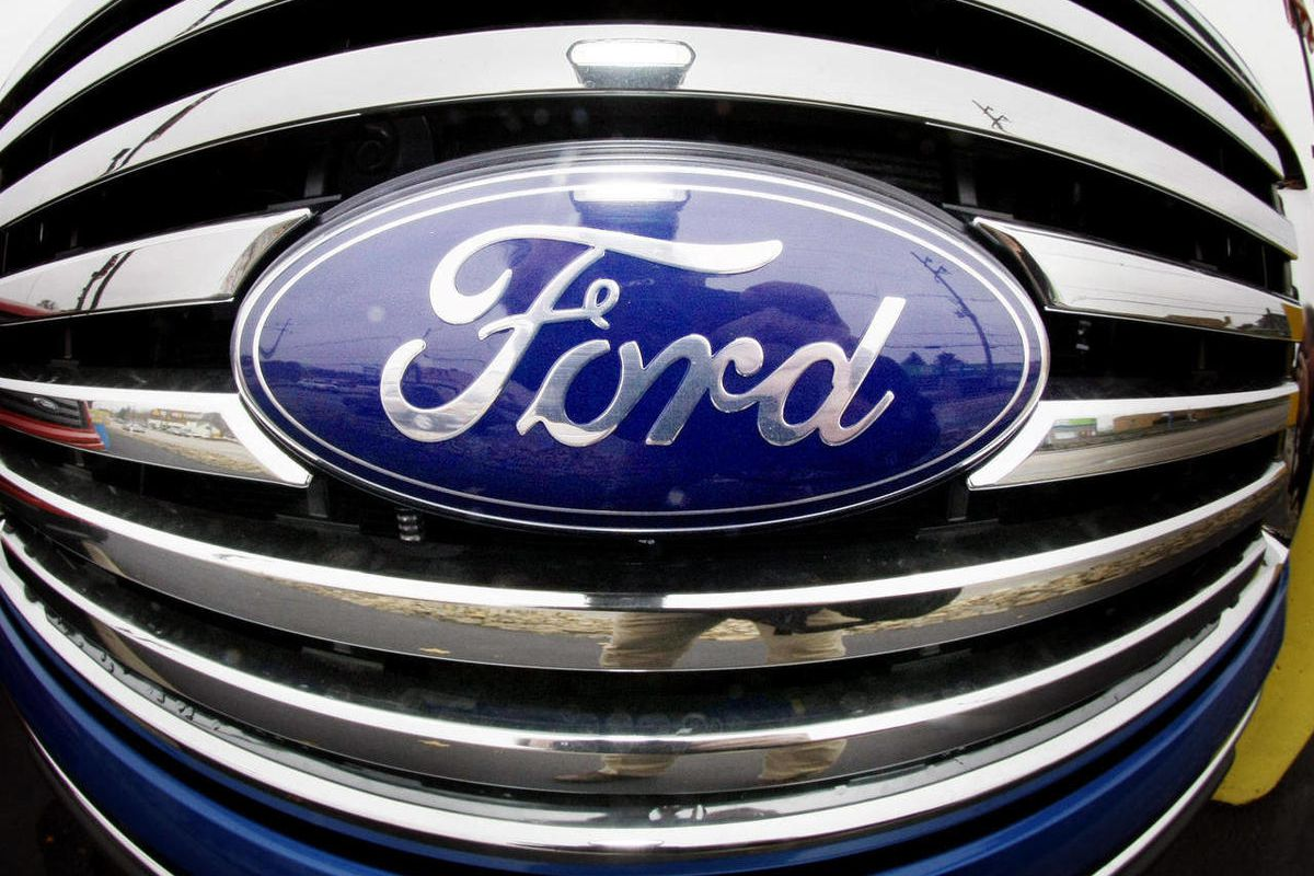 FILE - In this Oct. 29, 2009 file photo made with a fisheye lens, the Ford Blue Oval logo is shown on the grill of a pickup truck on a Ford dealership in Wexford, Pa. The Fitch Ratings agency lifted Ford's credit rating from junk status to investment grad