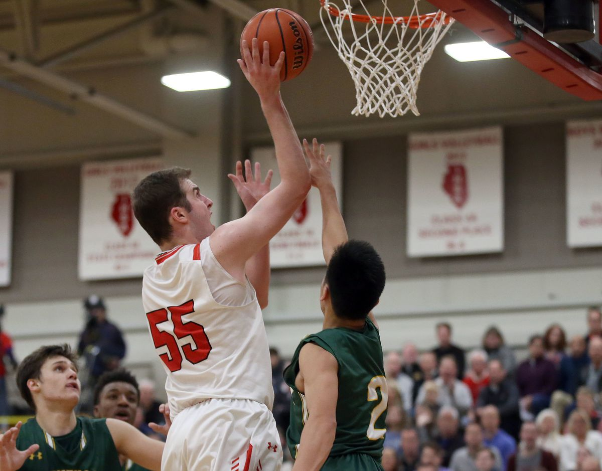 Benet's Colin Crothers (55) scores and is fouled by Stevenson's Luke Chieng (2).