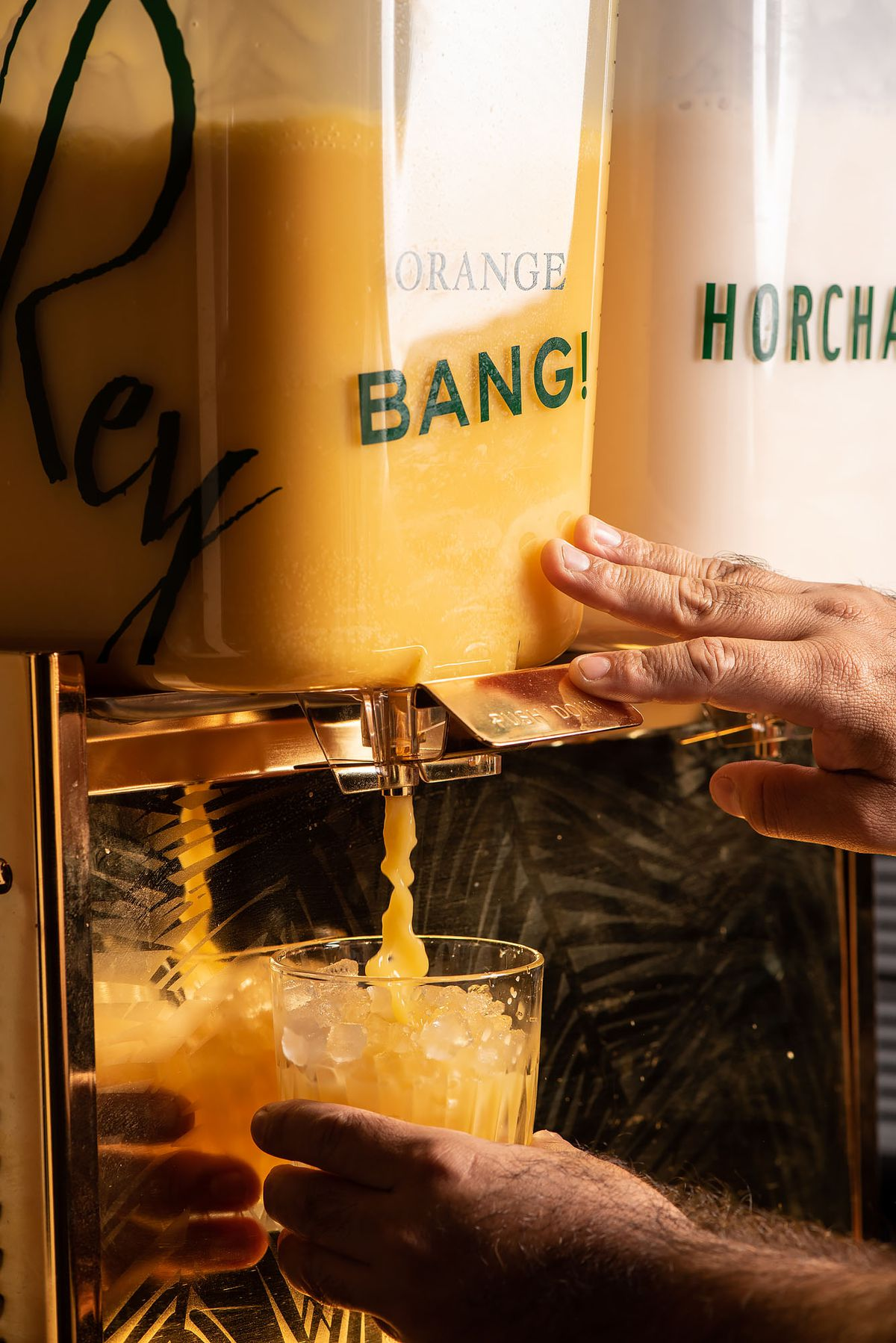 A dispenser pouring horchata and Orange Bang.