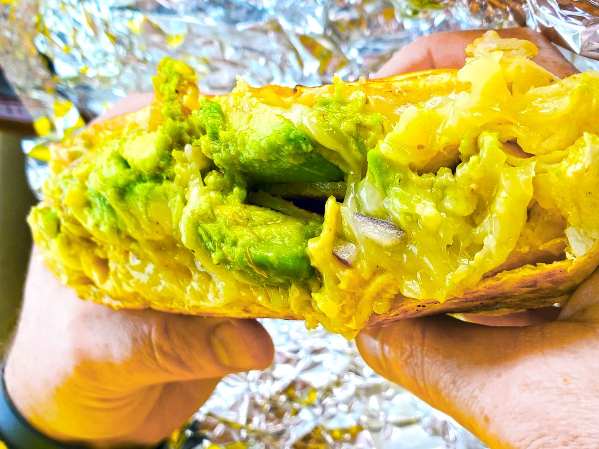 A wrap is seen held in two hands showing eggs and guacamole inside