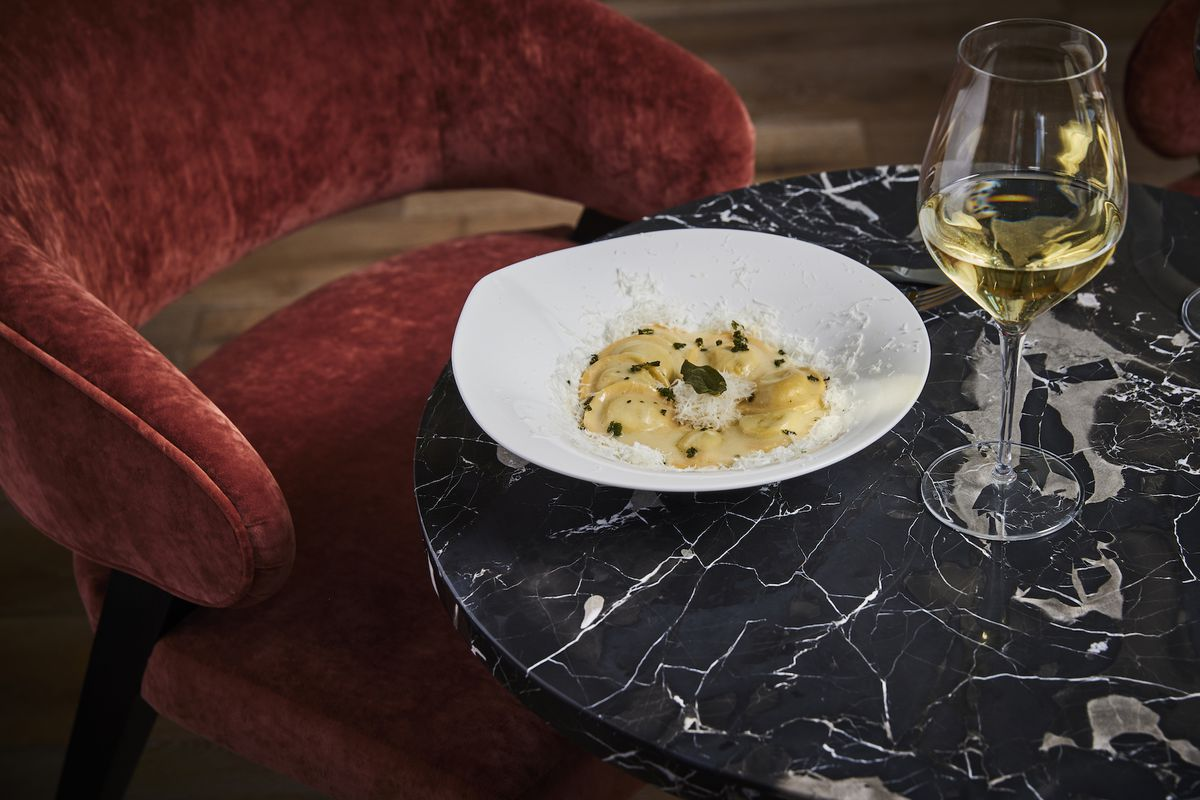 A dark restaurant space with pasta on a marble table and red chair beyond.