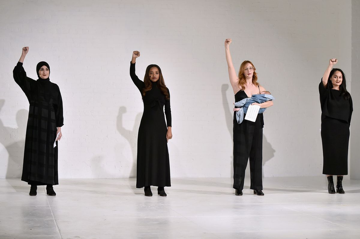 The four women throw their fists in the air.