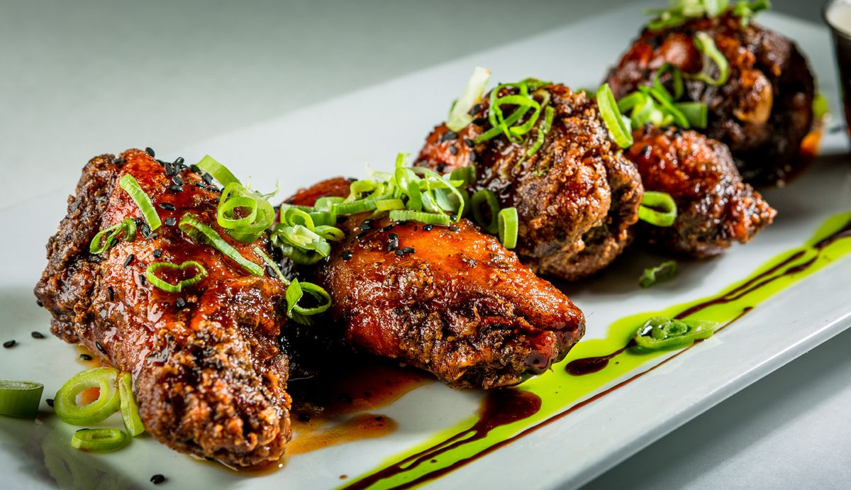 Crispy chicken wings line up side-by-side on a rectangular plate, topped with chopped scallions