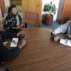 Aden Batar, right, speaks with refugees Nur Mataliga, left, and his wife Khadija Abdalla at Catholic Community Services in 2005.