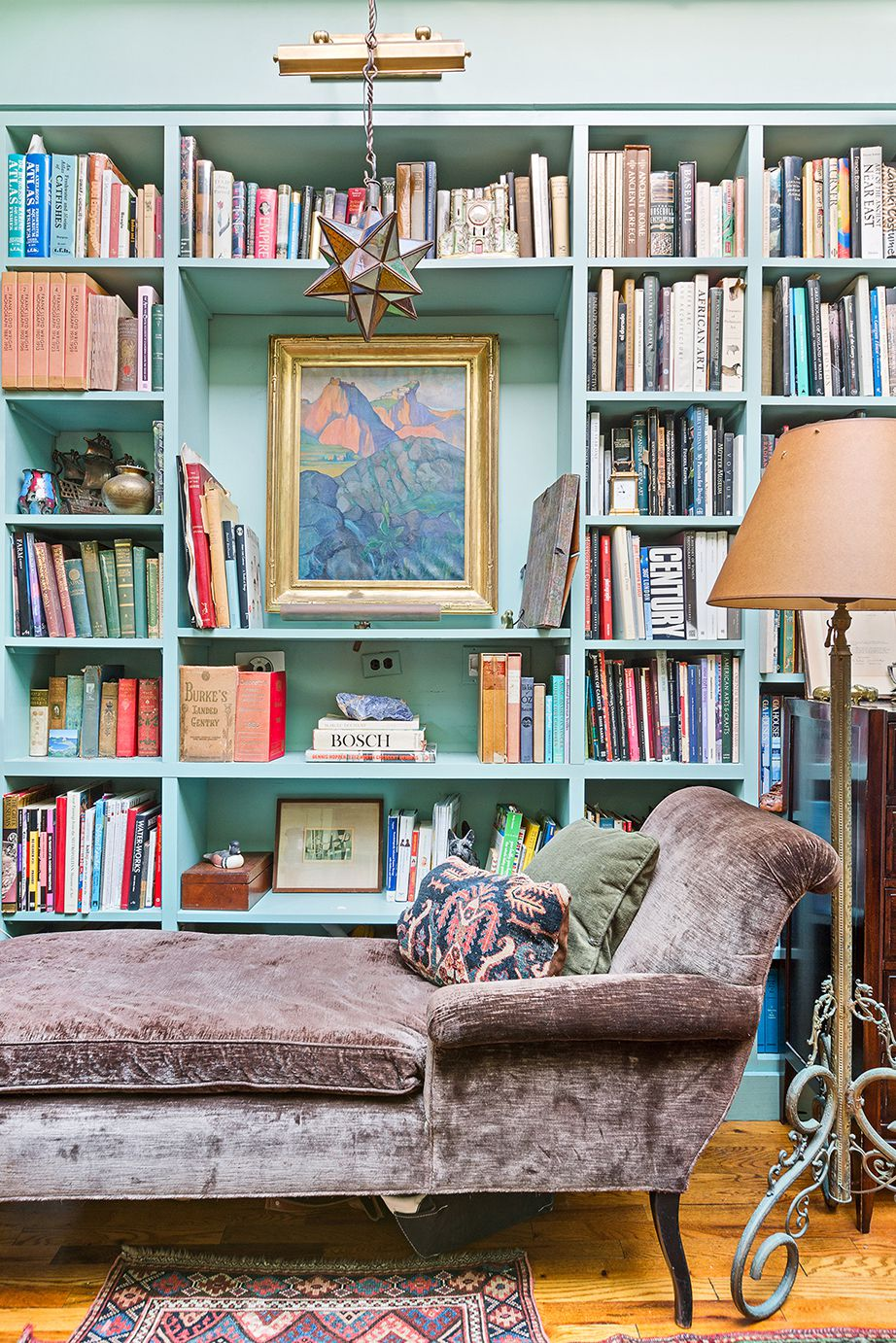 A living area with a brown couch, hardwood floors, a blue bookshelf, and a standing lamp.