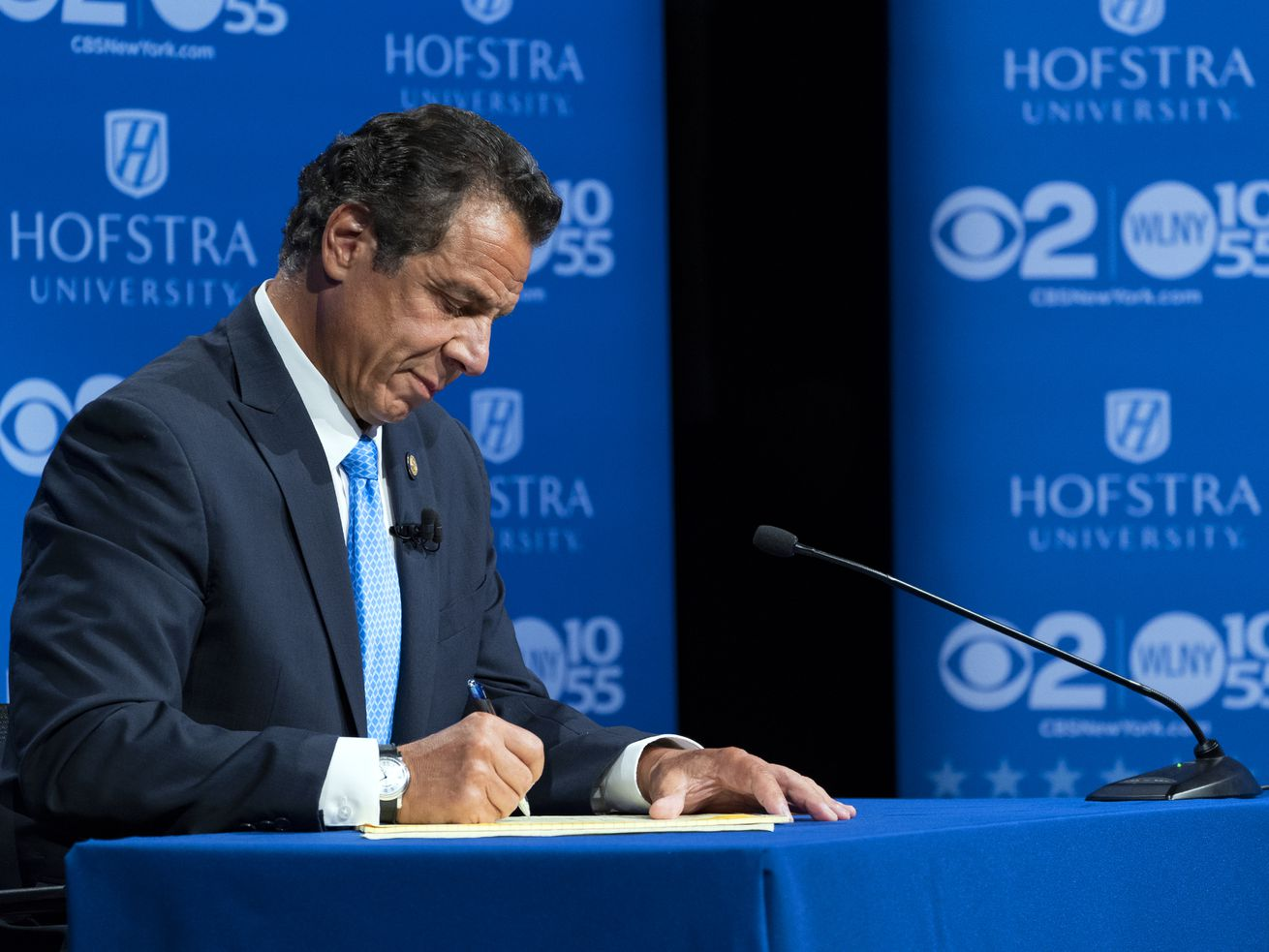 New York Gov. Andrew Cuomo takes notes during a primary debate with opponent Cynthia Nixon at Hofstra University on August 29, 2018.