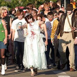 """A crowd of zombies """"spooks"""" a passing car near Mount Olivet Cemetery before heading to Trolley Square."""