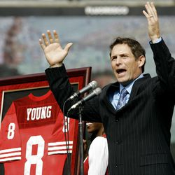 NFL Hall of Famer and former San Francisco 49ers quarterback Steve Young gestures to fans as his No. 8 is retired during a halftime ceremony at the 49ers' NFL football game against the New England Patriots on Sunday, Oct. 5, 2008, in San Francisco.