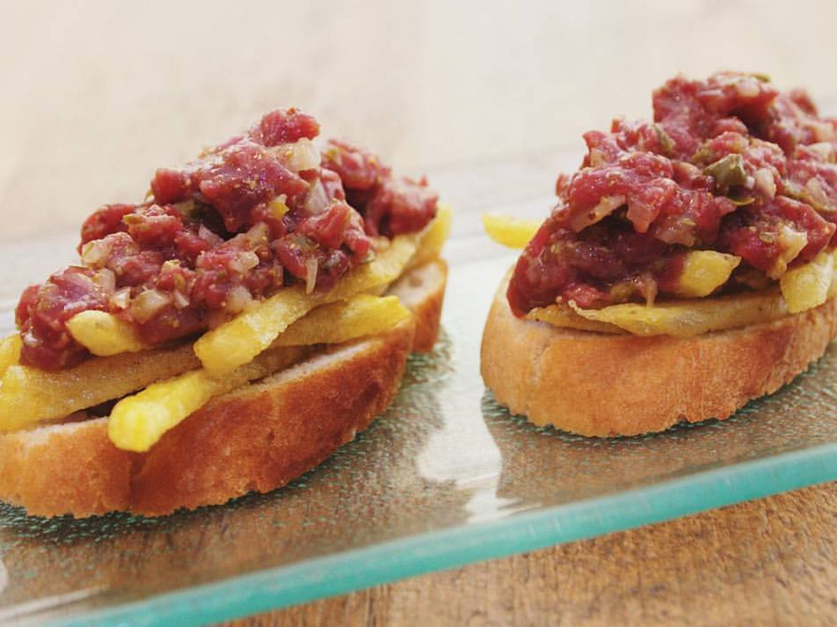 Slices of bread topped with french fries and steak tartare, arranged on a glass plate