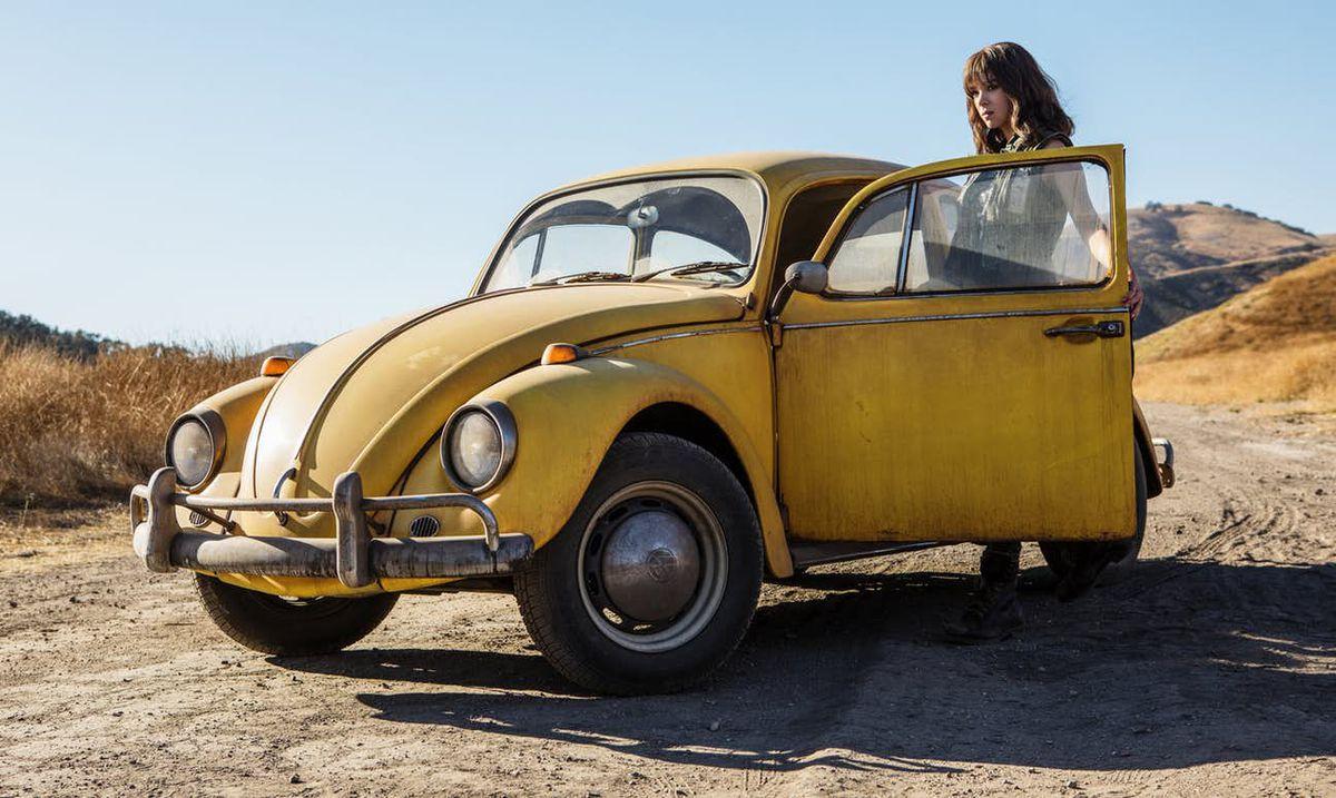Bumblebee - Charlie Watson standing next to her Volkswagen Beetle