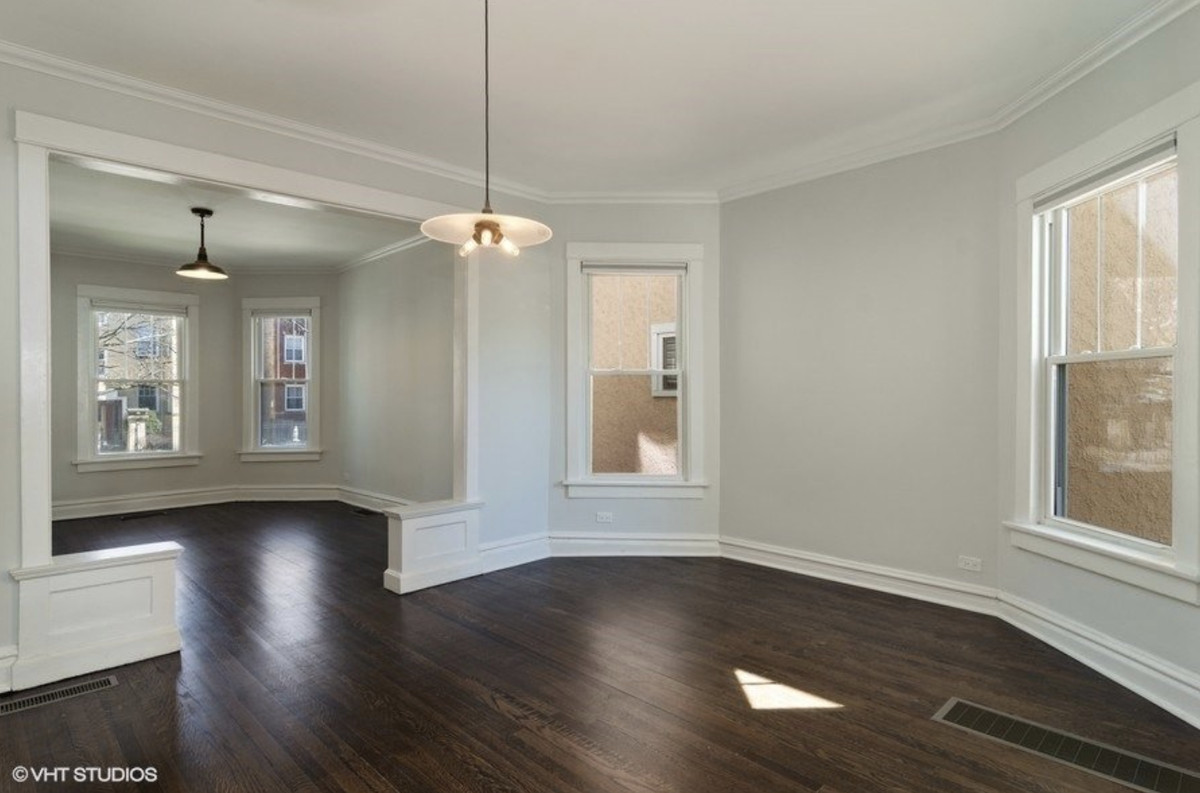 A view of the dining room and living room. There is dark hardwood floor and large windows.