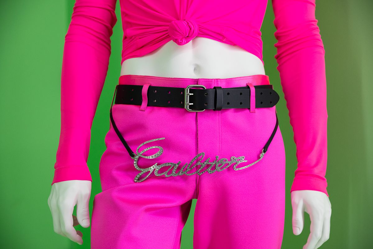 """A hot pink pair of pants with a black belt that says """"Gaultier"""" in metal and crystals."""