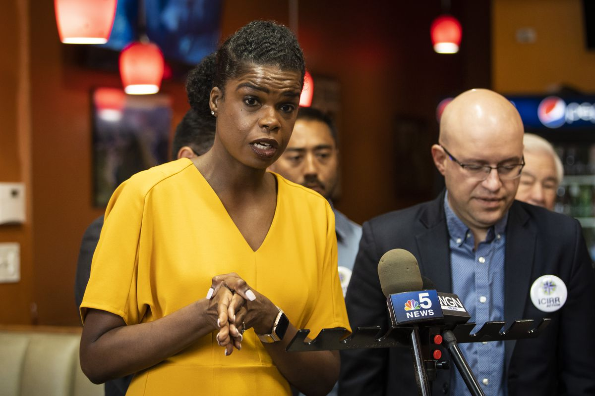 Cook County State's Attorney Kim Foxx speaks to reporters during a campaign stop at Cecina Grill in Pilsen as Ald. Michael Rodriguez (22nd), right, listens.