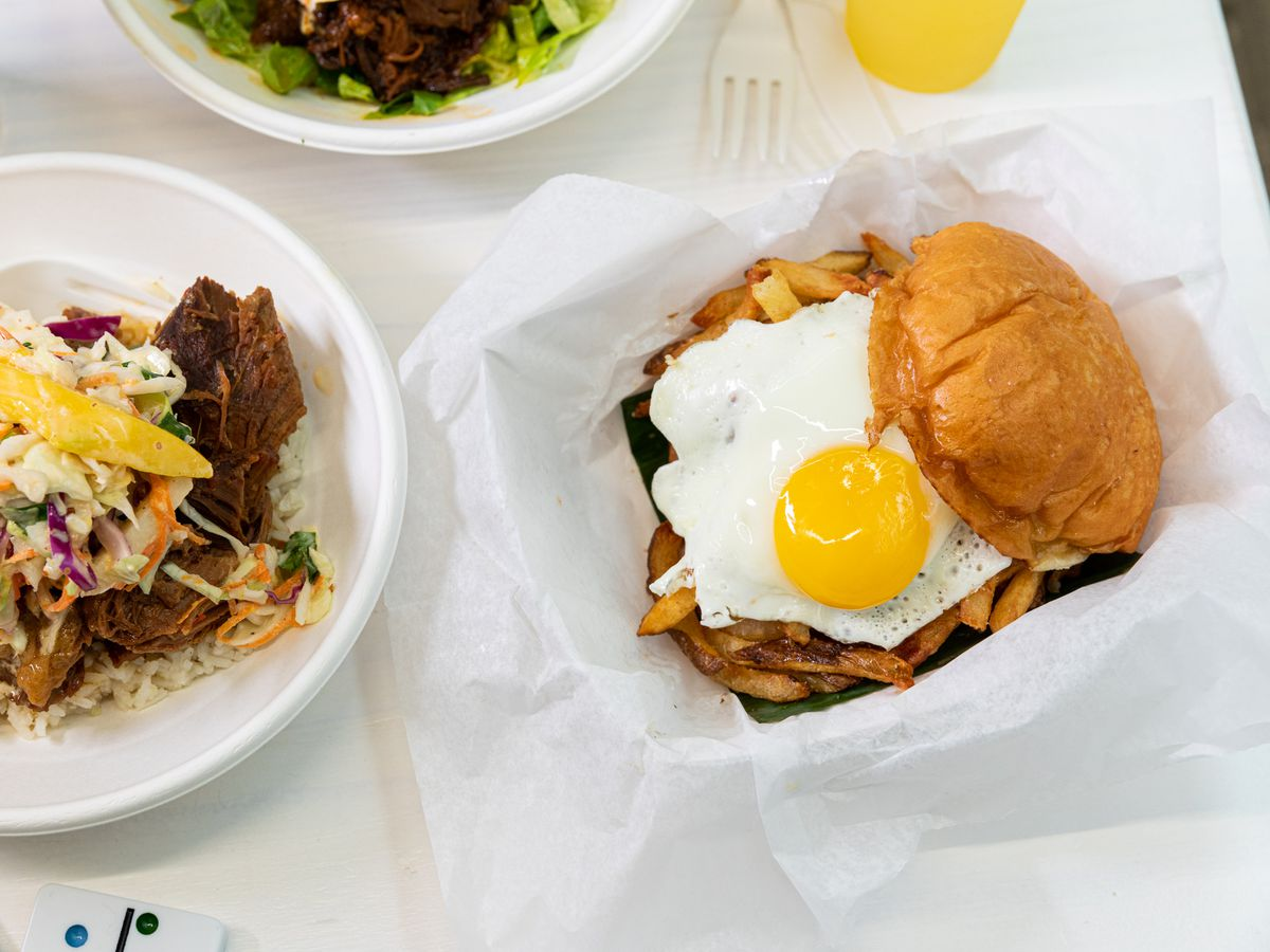 A rice bowl with some type of meat, coleslaw, and veggies sits next to a basket with a beef burger topped with fries and a fried egg.