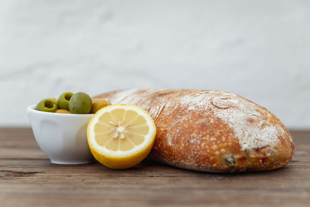 A loaf of bread with a cut lemon and bowl of green olives.