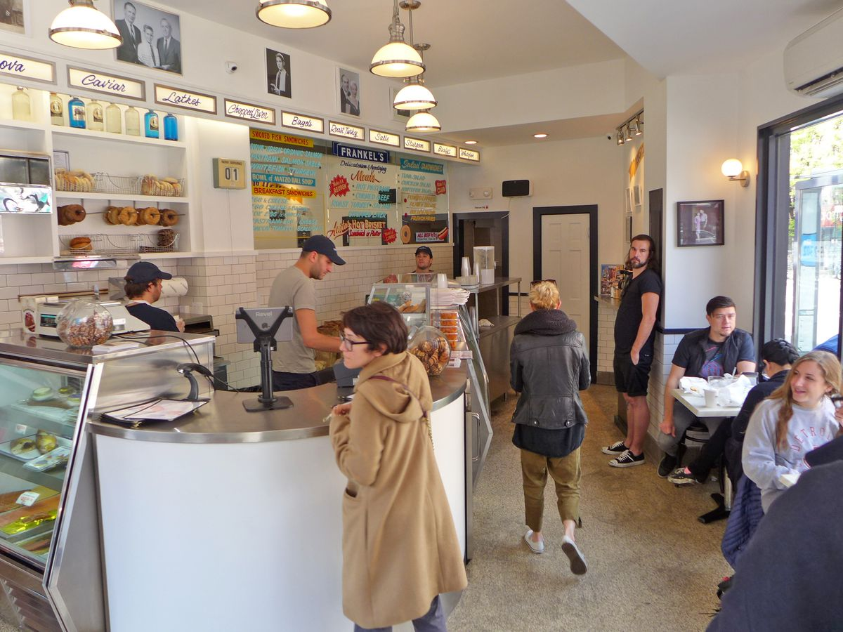 A woman stands at the counter of a small cafe, bagels are hung on the wall, as are a series of neon signs that read: Nova, Caviar, Latkes, Chopped Liver, and Bagels