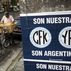 """A sign reading in Spanish """"They are ours. CFK. YPF. They are Argentine"""" hangs in Buenos Aires, Argentina, Tuesday April 17, 2012. President Cristina Fernandez pushed forward a bill to renationalize the country's largest oil company on Monday despite fierce criticism from abroad and the risk of a major rift with Spain.  Fernandez said the legislation put to congress would give Argentina a majority stake in oil and gas company YPF by taking control of 51 percent of its shares currently held by Spain's Repsol."""