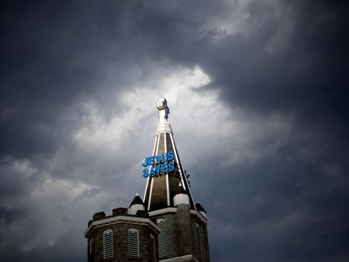 """Church steeple with blue """"Jesus Saves"""" sign on it."""
