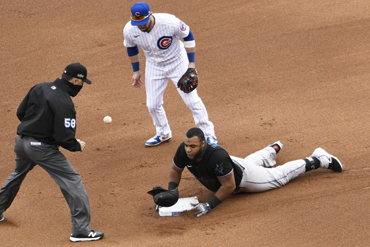 Miami Marlins designated hitter Jesus Aguilar (24) slides safely into second base with a double as Chicago Cubs second baseman Jason Kipnis (27) takes the throw during the fourth inning at Wrigley Field.