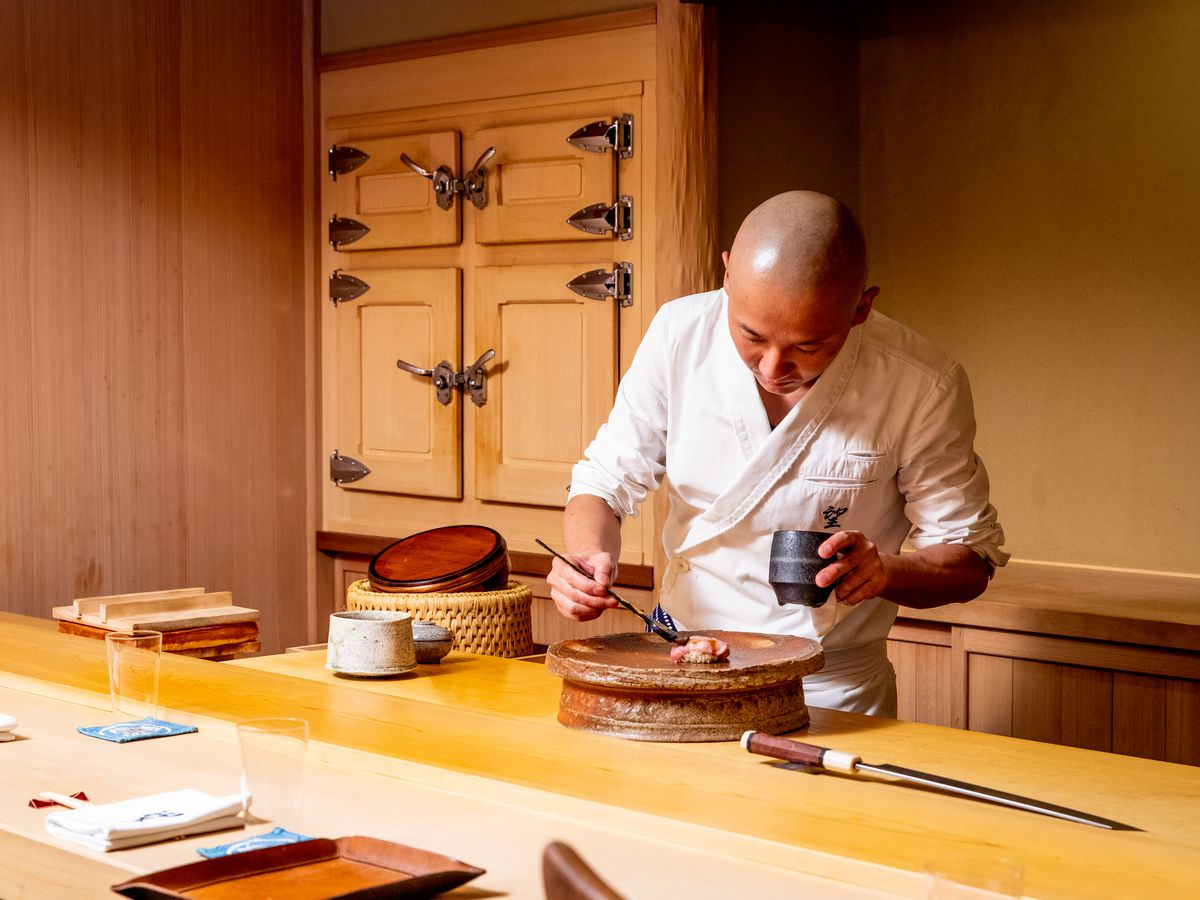 Chef Nozomu Abe brushes a slice of fatty tuna sushi with a soy reduction