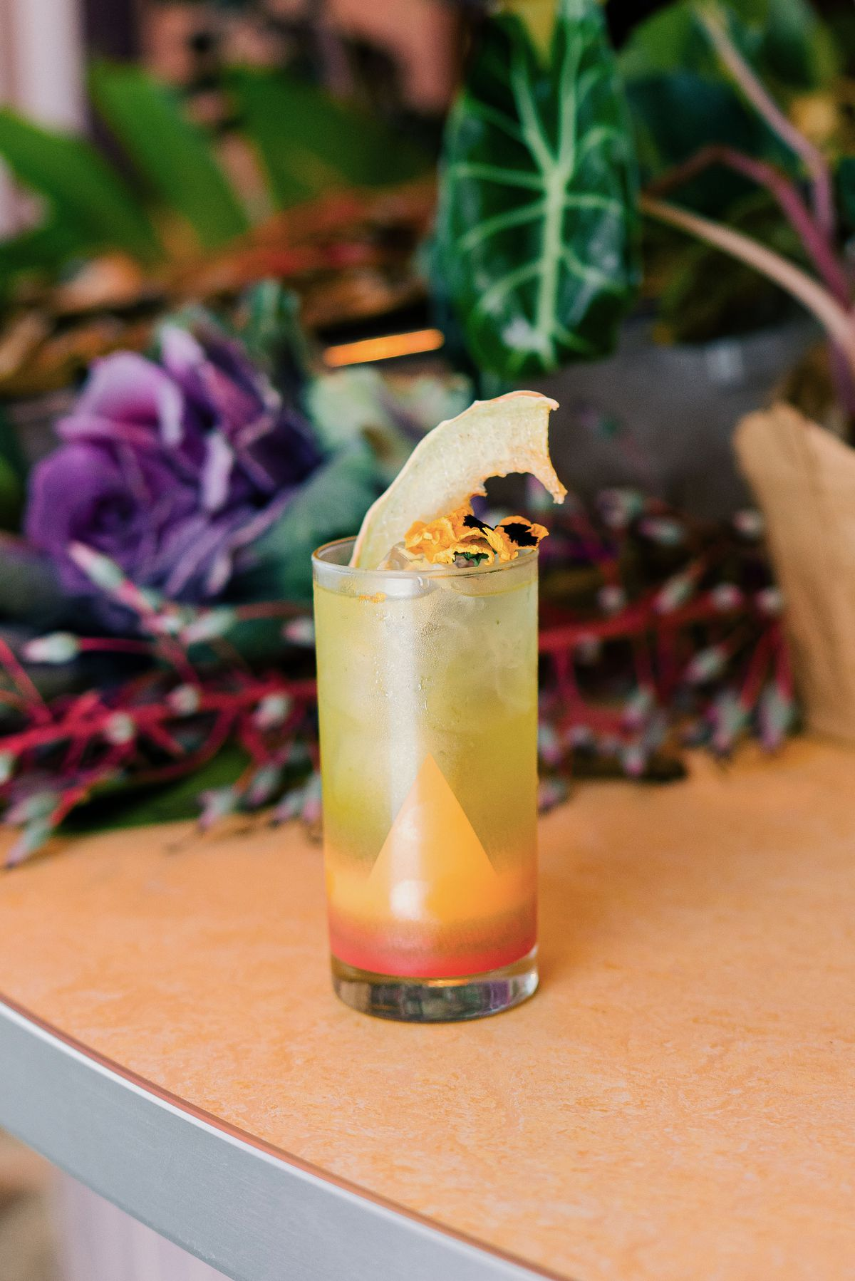 yellow cocktail on table with flowers in background