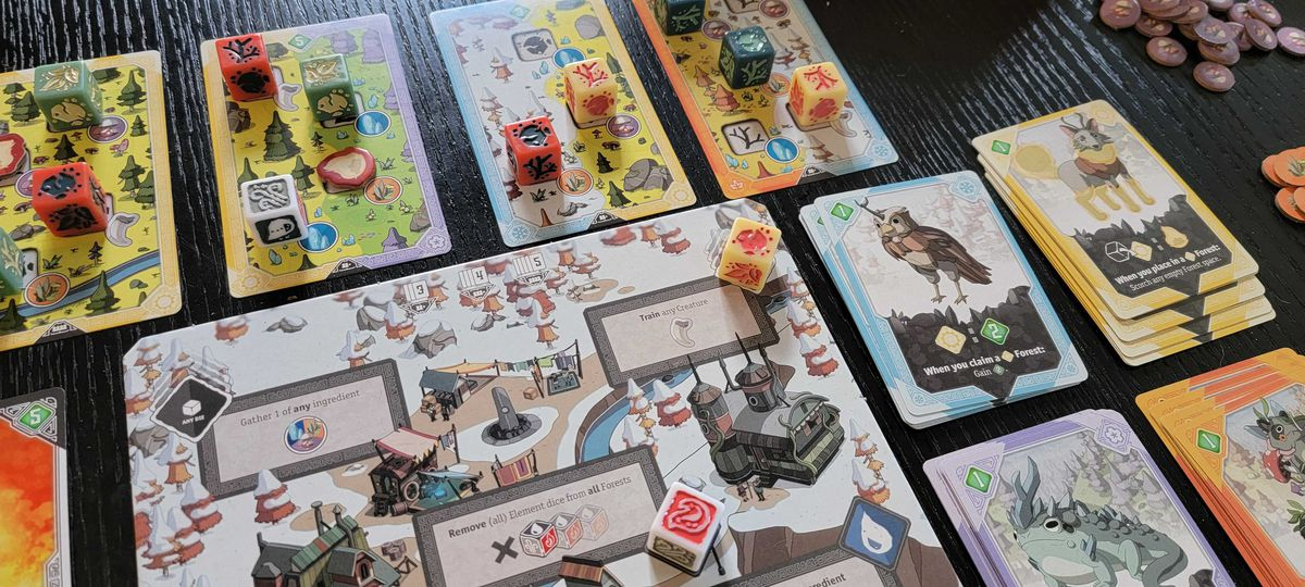 A game of Brew set up for play, including specialized dice set on colorful cards. The art shows a horned owl and a wolf with yellow boots.