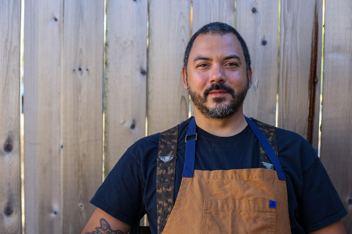 A man with short hair and facial hair wearing a dark T-shirt and light brown apron standing in front of a wooden fence