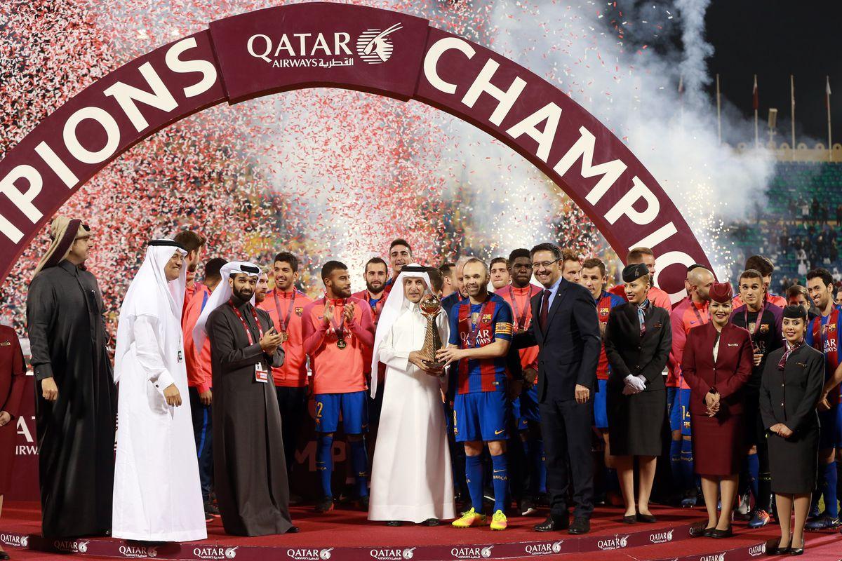 Qatar airways CEO Akbar Al Baker (C) presents the trophy to Andres Iniesta (5th R) of Barcelona after winning the friendly soccer match between Al-Ahli Saudi and Barcelona at Al-Gharrafa Stadium in Doha, Qatar on December 13, 2016.