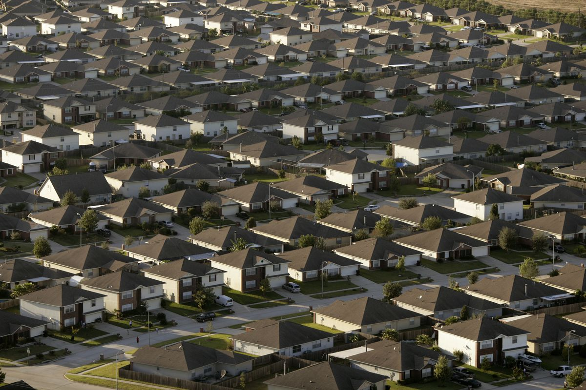 Rows and rows of suburban tract homes in Houston that are almost uniform in size and scale are seen from the air.