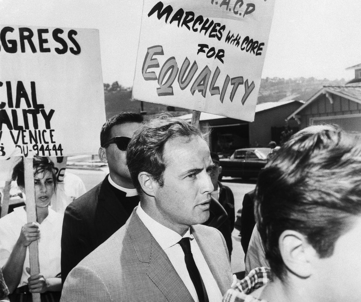 """A close-up of actor Marlon Brando, dressed in a suit, marching with protestors. Homes are visible in the background. Marchers are carrying signs that say """"Marches with CORE for Equality."""""""