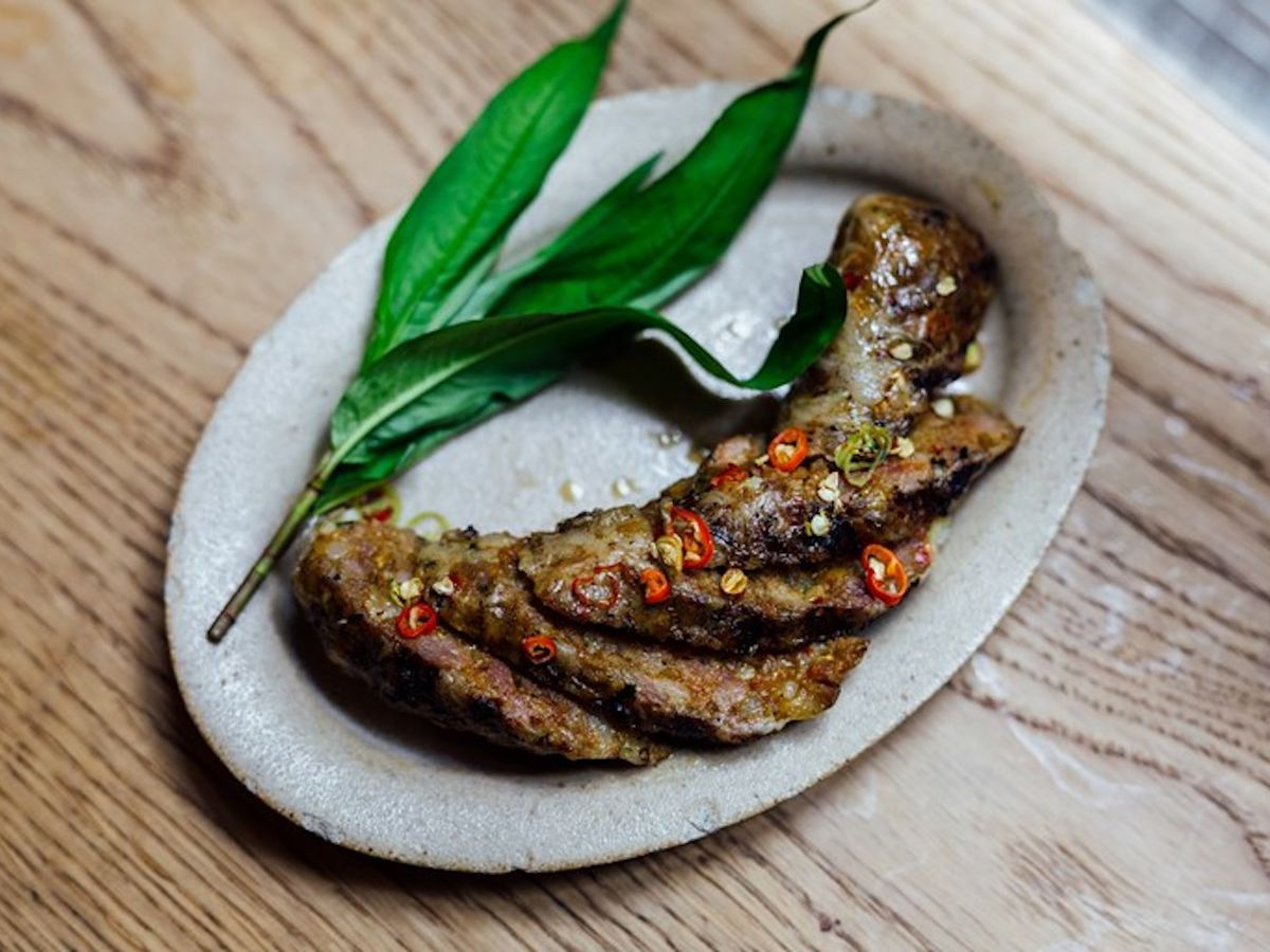 A sliced Thai sausage on a platter scattered with chilli