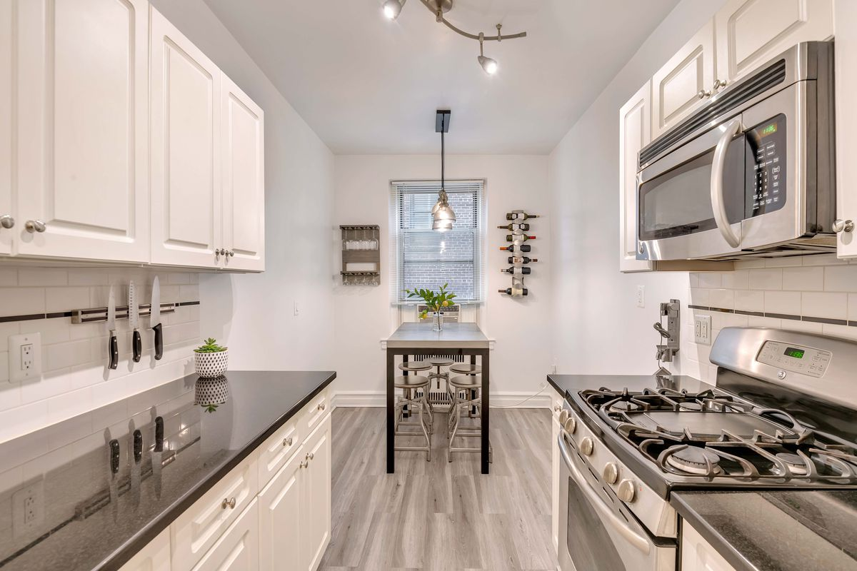A kitchen with white cabinetry.