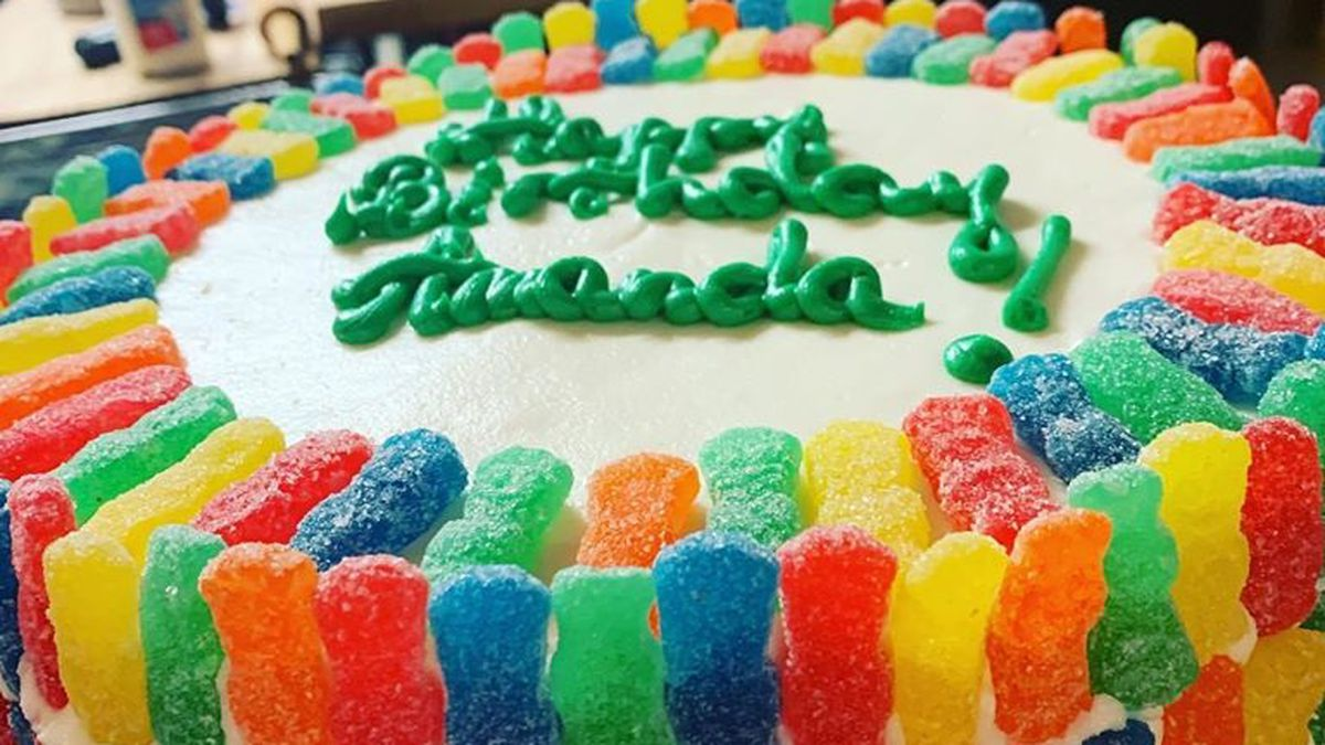 A white cake with a birthday inscription covered with gummy bears.