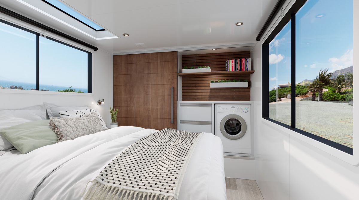 A white bed sits between windows on either wall, a washer and dryer, and a walnut-finished closet for clothes.