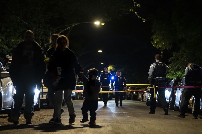 A family walks by as Chicago police investigate in the 3700 block of West McLean Avenue in Logan Square, where authorities said a 29-year-old man was shot multiple times Saturday night.