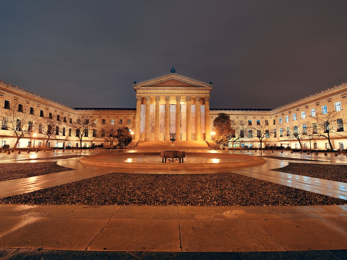 The exterior of the Philadelphia Museum of Art. The museum has columns flanking the entryway and a large courtyard in front.