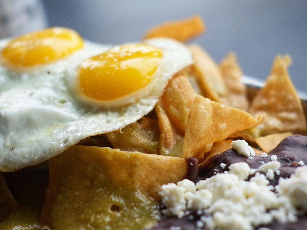 An up close shot of a plate of chilaquiles — tortilla chips, black beans, two fried eggs and queso fresco.